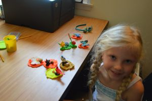 Lillian making play dough nests for her birds